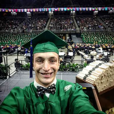 MSU advertising alumni Derek Black taking a selfie at commencement ceremony.