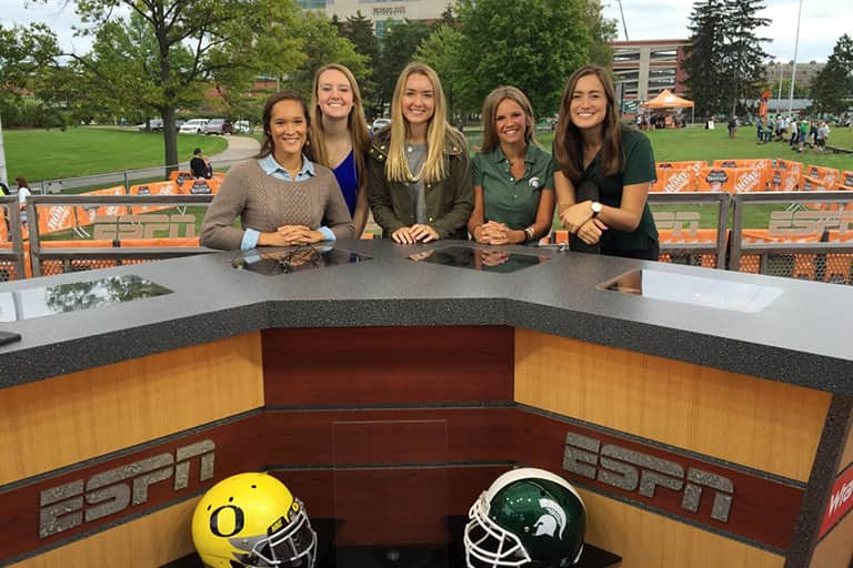 Journalism students on ESPN GameDay desk before MSU football game.