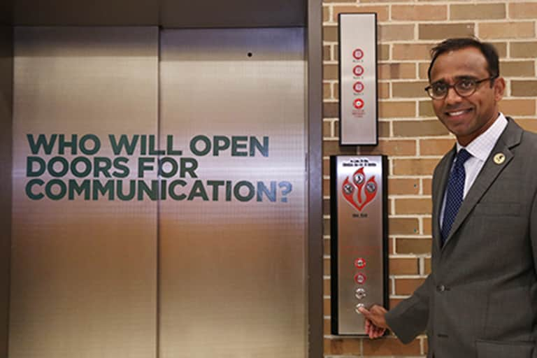 Dean Prabu David standing in front of the south lobby elevators. Elevator doors have sign on it that reads, who will open the doors for communication?