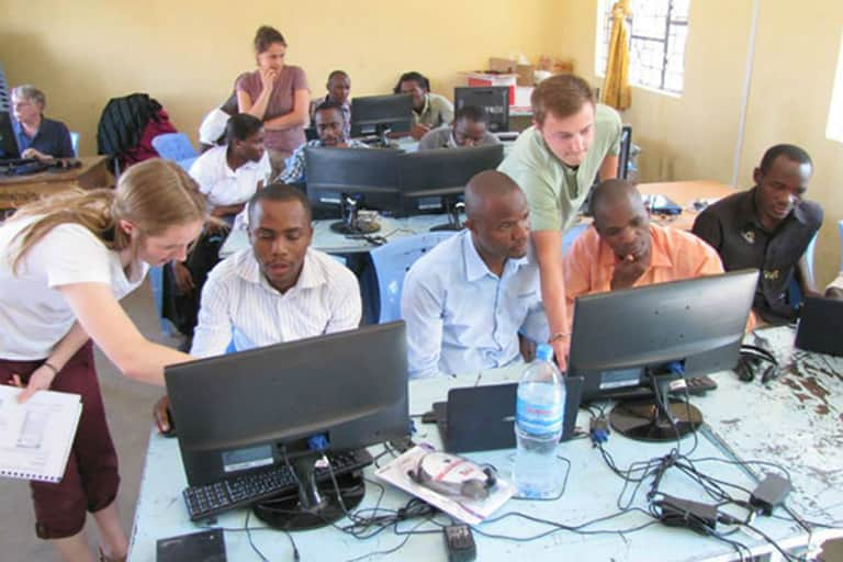 MSU students assisting Tanzania students on computers in classroom.
