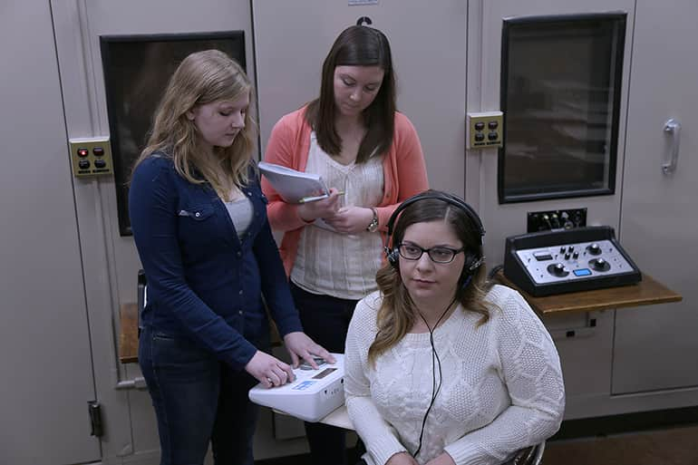 Two female undergraduate students performing a hearning test on another student.