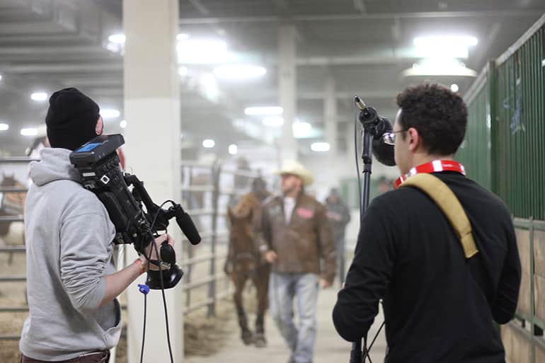 Two male students from Media and Information class 491: Live Event Production for Broadcast, shooting the Spartan Stampede, a professional rodeo.