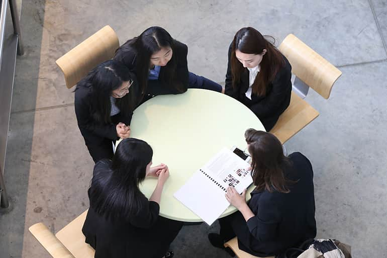 Four female students sitting at a round table working with client on a presentation.
