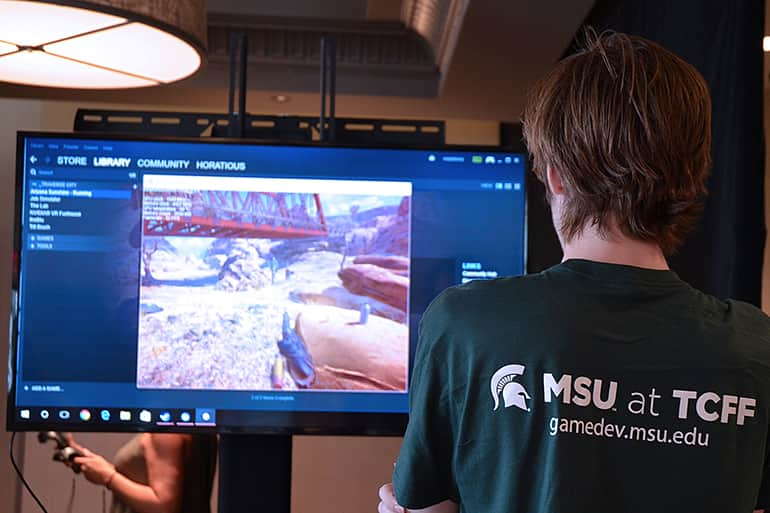 Game design student playing a MSU designed game at the Traverse City Film Festival.
