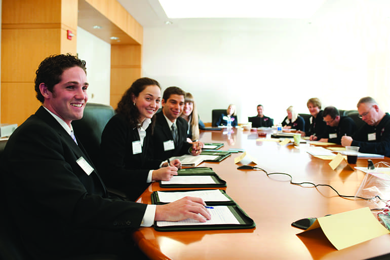 A group of sales leadership students sitting at a long conference table working with local clients.