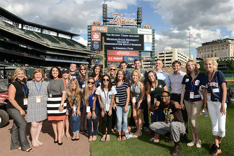 A large group of advertising students in the field of the Detroit Tiger Baseball stadium.
