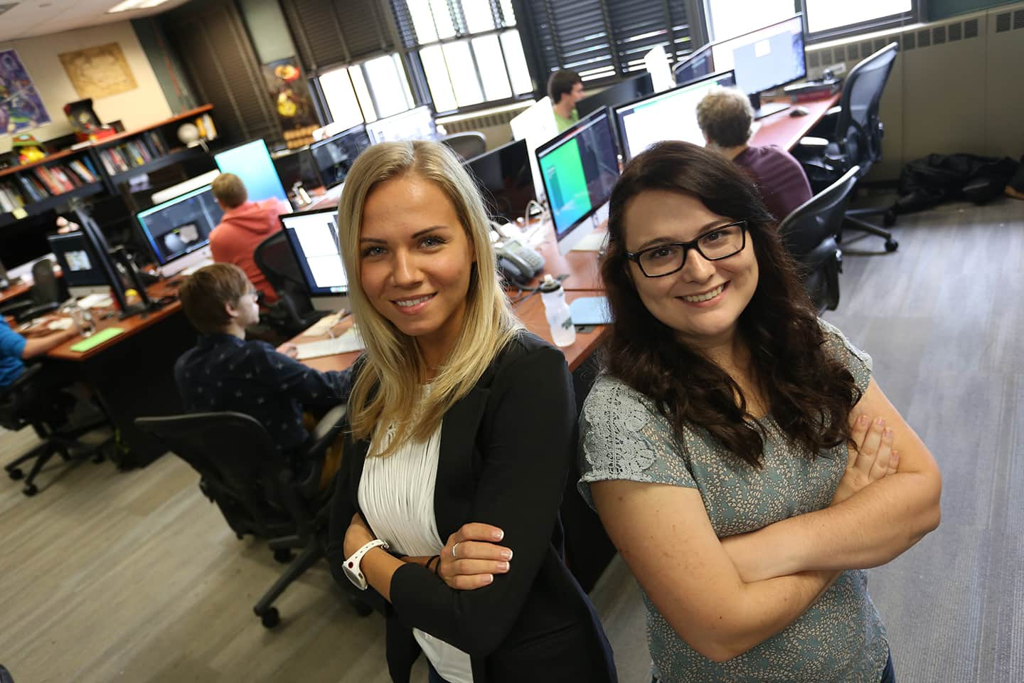 Two female game design graduate students standing next to one another in the GEL Lab.