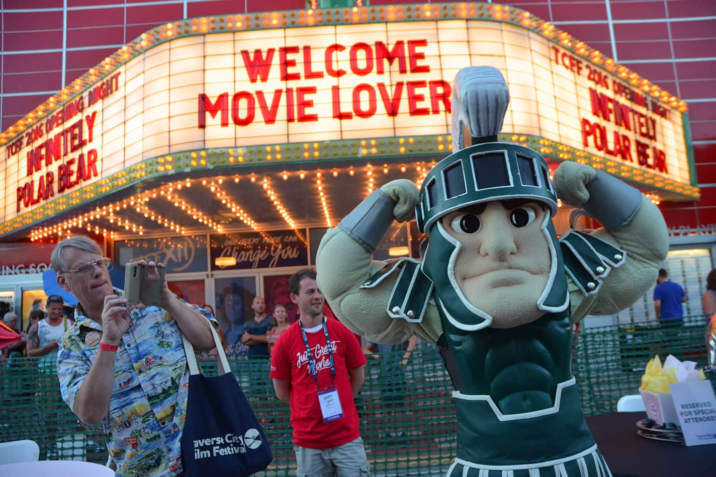 MSU Sparty standing in front of a movie theater in Traverse City for the film festival showing some muscle.