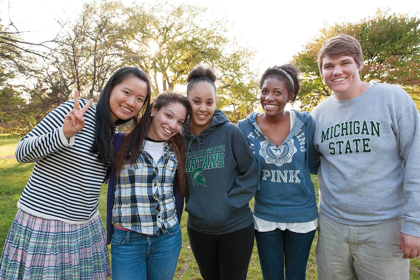 Four female multi-ethnic and one white male ComArtSci students standing together outside on msu campus.