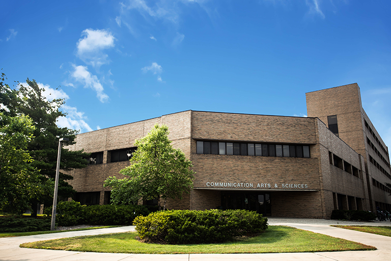 Photograph of the ComArtSci building on a clear summer day with a bright blue sky.