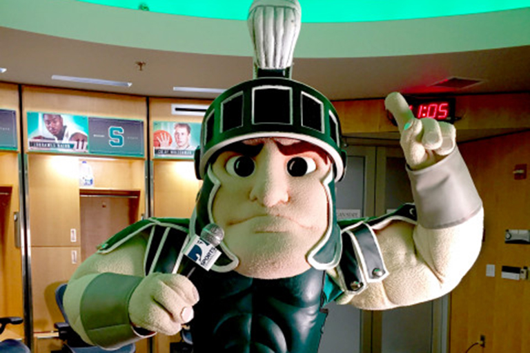 The MSU mascot, Sparty, raising his hand.