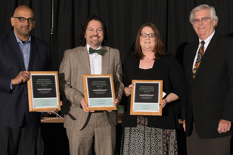 Jeremy Steele, left center, and Joy Visconti. right center, receive an Outreach and Engagement award.