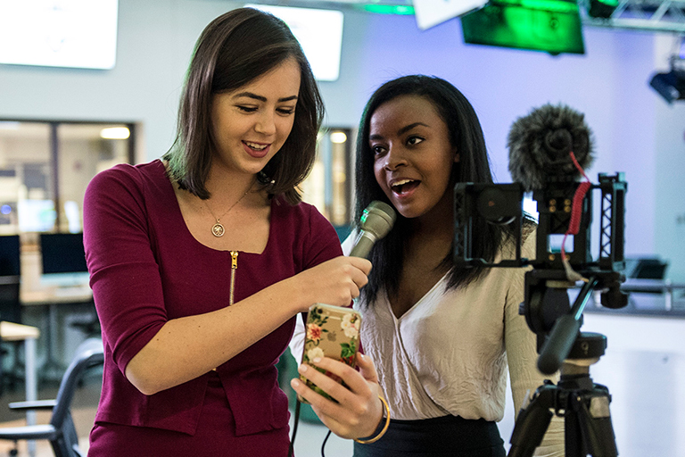 Two female journalism students prepare for on camera assignment.