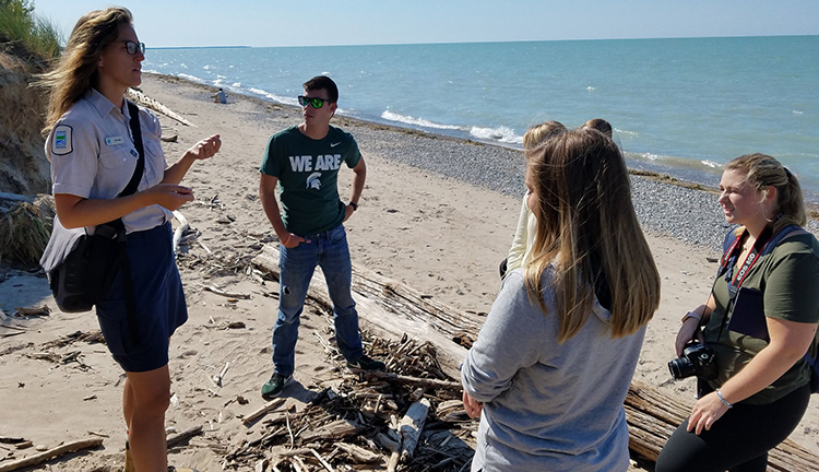 Michelle Polley, a naturalist at Pinery Park in Ontario, discusses skinks, toad balloons, marram grass, hognose snakes and karner blue butterflies with Knight Center students on a Lake Huron beach. The students traveled to Canada to study transboundary issues. From left Remington Sawege, Kaley Fech, Whitney McDonald, Quinn Zimmerman, Alexandria Iacobelli and Anntaninna Biondi.