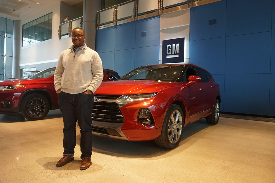 Photo of MSU StratCom student Dan Peake in front of a red car at GM