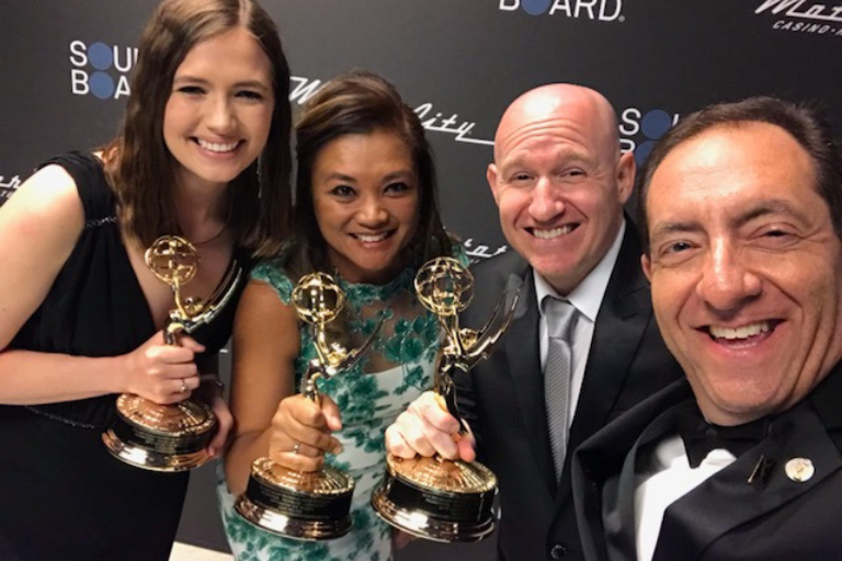 "The team for ""Sh*t Saves the World"" proudly holding their Emmys on the red carpet"