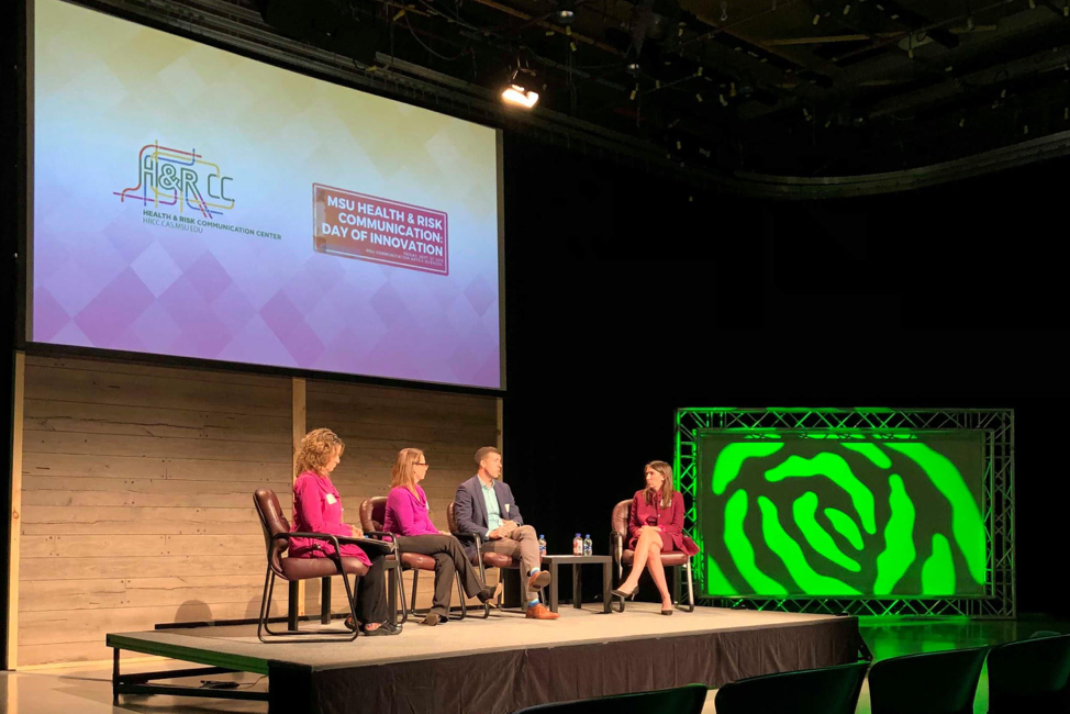 The three panelists with Maria Lapinski on a lit stage in front of a projector screen