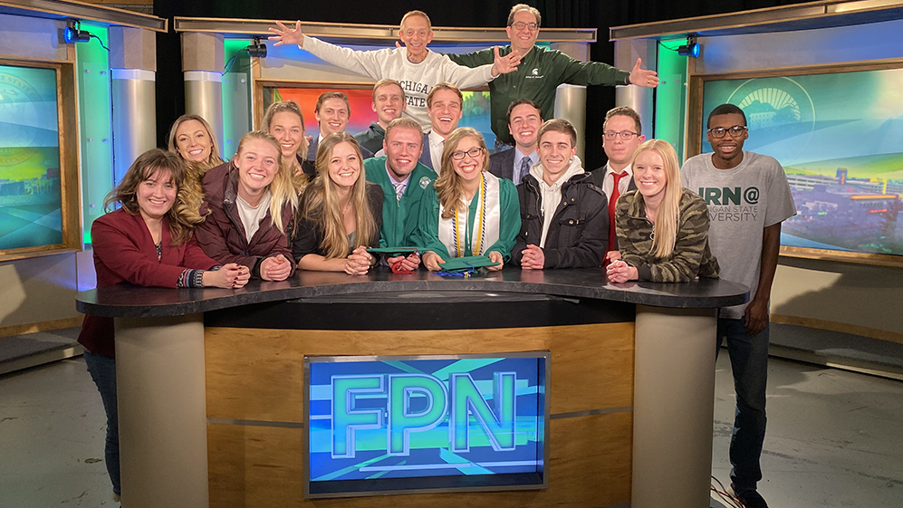 MSU School of Journalism broadcast students pose at the anchor desk of the Focal Point broadcast studios.