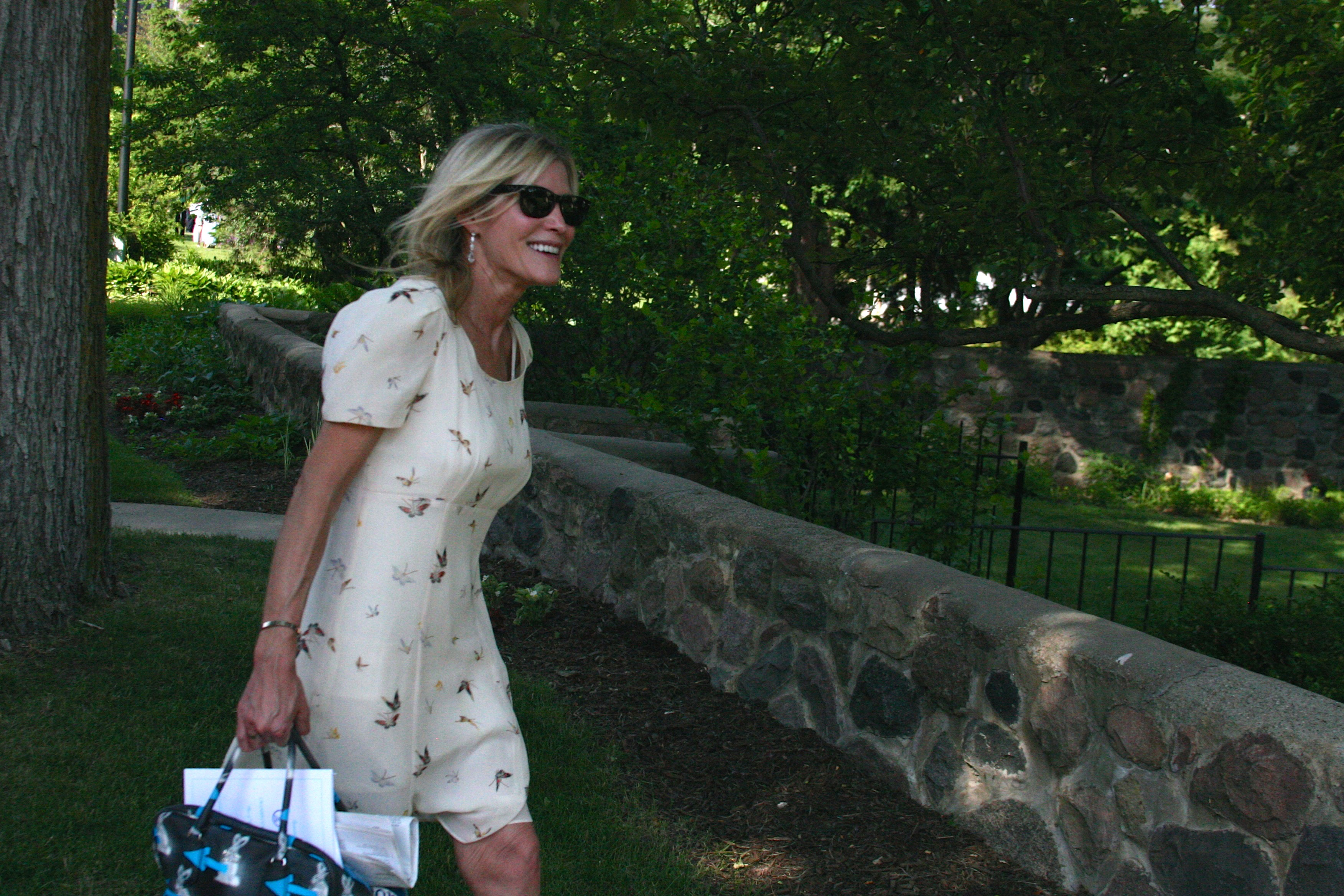 Kogler set against a backdrop of trees, smiling and holding a purse and wearing sunglasses