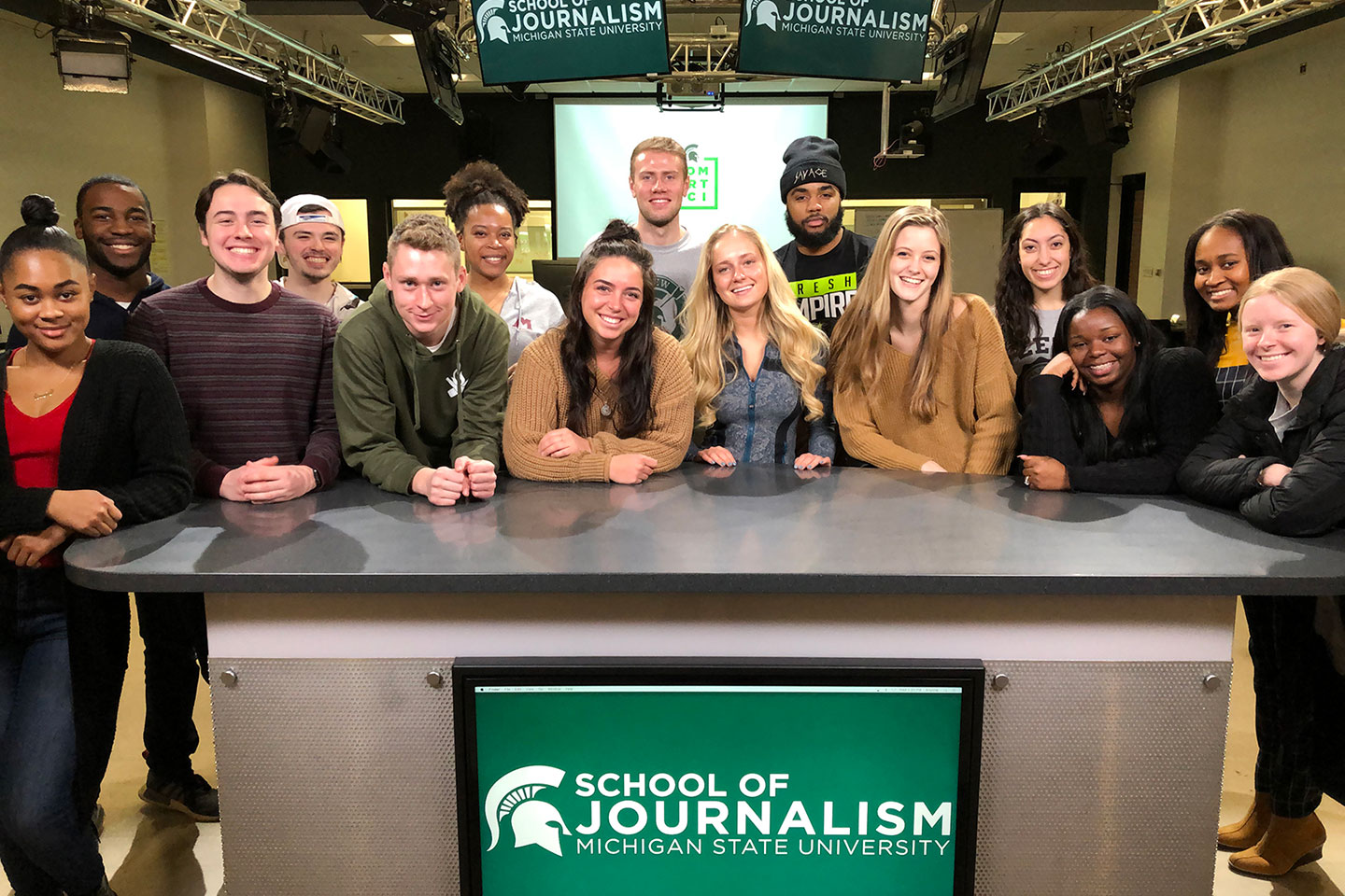 A group of journalism students working in the newsroom