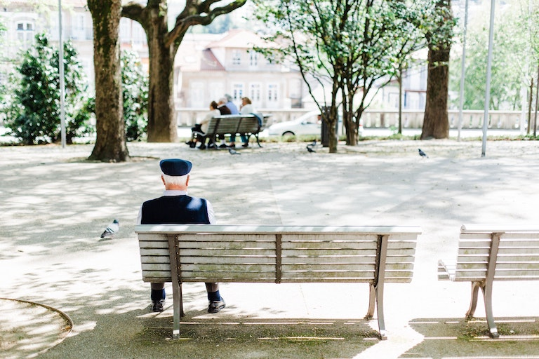 Photo of an elderly man sitting on a bench watching people in the park