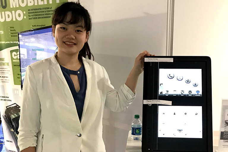 Jinghan Ni poses with her prototype at the Detroit Auto Show.