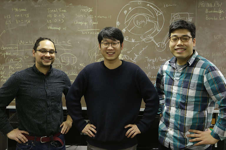 Ratan, Lee and Park stand smiling in front of a chalk board