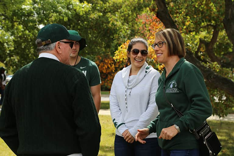Alumni and faculty talk during the annual CSD tailgate.