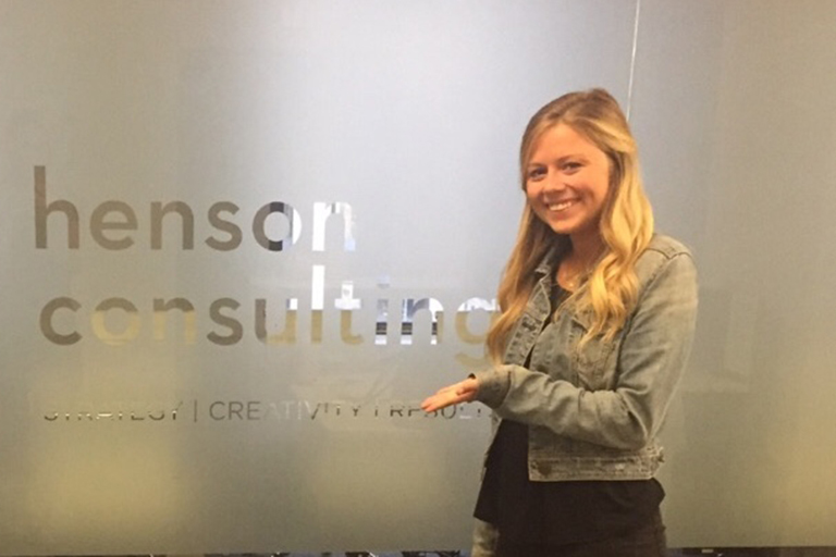 Alexandra DeVilling posing in front of the Henson Consulting sign.