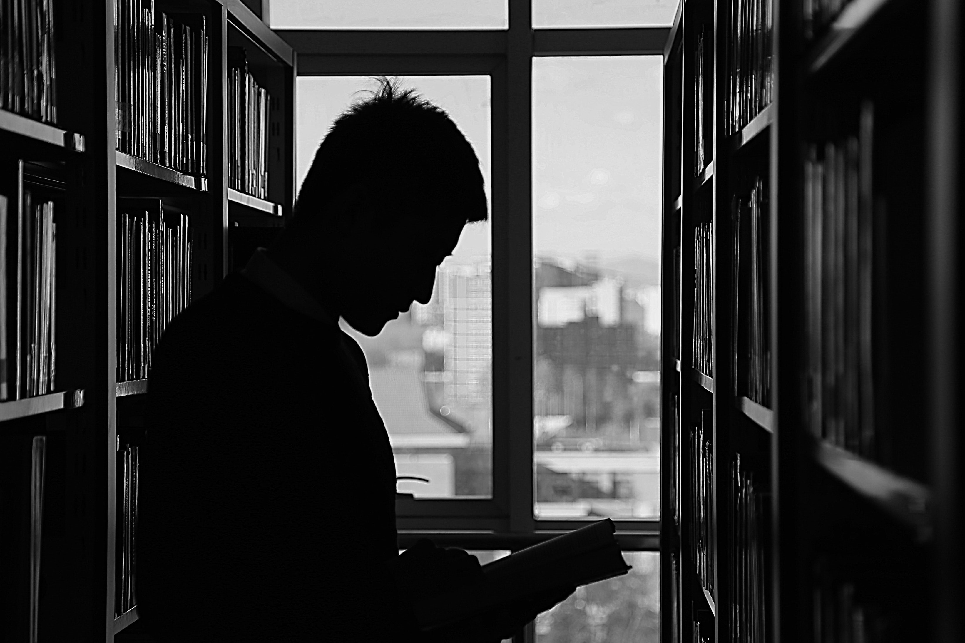 student reads a book in between two shelves at the library