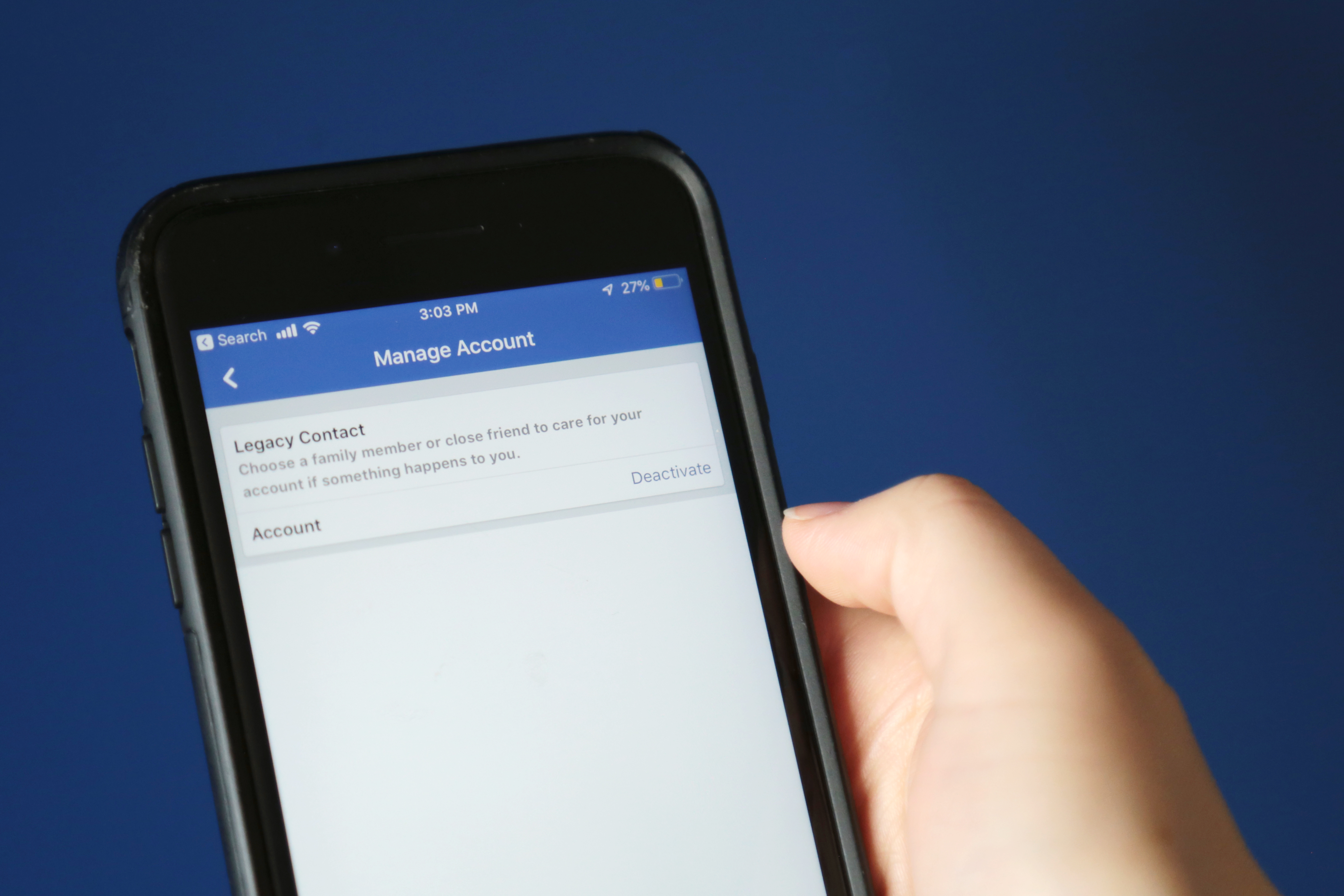 Photo of hand holding phone with Facebook app and Deactivate button showing