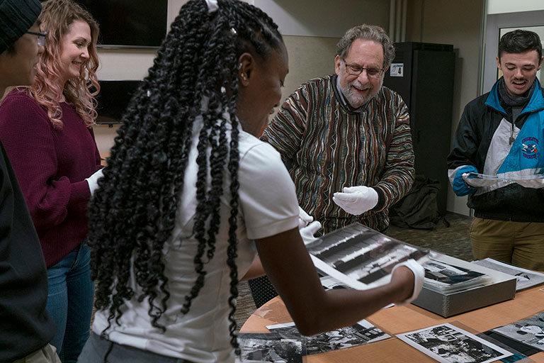 Students looking at photographs of post-Apartheid South Africa made by the late Leonard Freed, an important 20th century photojournalist. The photographs are housed in MSU Special Collections.