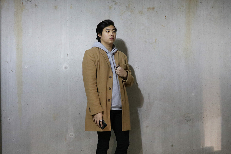 Advertising junior Toraki Maehata posing in a jacket in front of a cement wall.