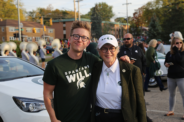 ComArtSci alumnus Tyler Oakley stands in front of his parade car with his arm around MSU President Simon.
