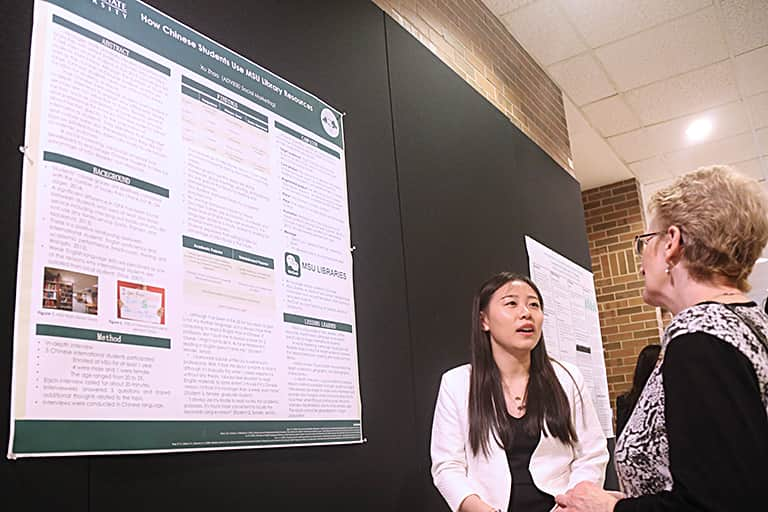 Advertising graduate student discusses her research with professor.
