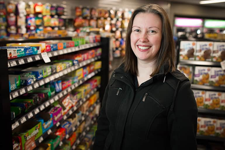 Professor Anna McAlister smiling as she stands next to snack items in grocery store.