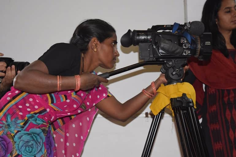 indian women behind movie camera shooting a scene.