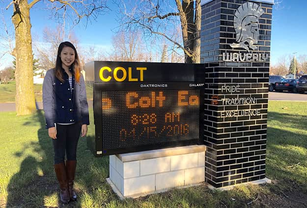 Joni Choi standing outside next to the Colt School sign.