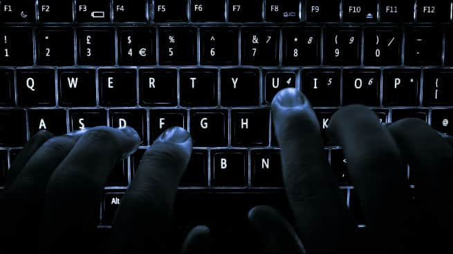 Person typing on computer keyboard.