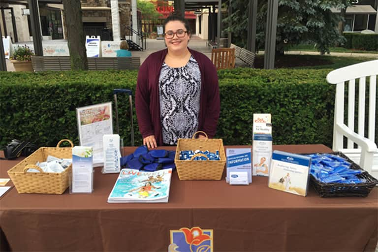 Erika standing outside behind table display of books and other marketing materials.