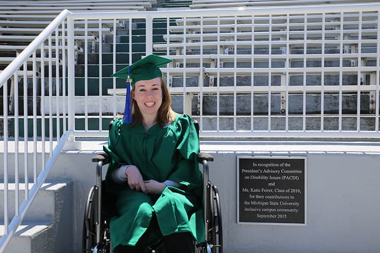 "Katie Feirer sitting in wheelchair at MSU Spartan Stadium next to the plaque. The plaque reads, ""In recognition of the President's Advisory Committee on Disability Issues and Ms. Katie Feirer, Class of 2016, for their contributions to the MSU inclusive campus community. September 2015."