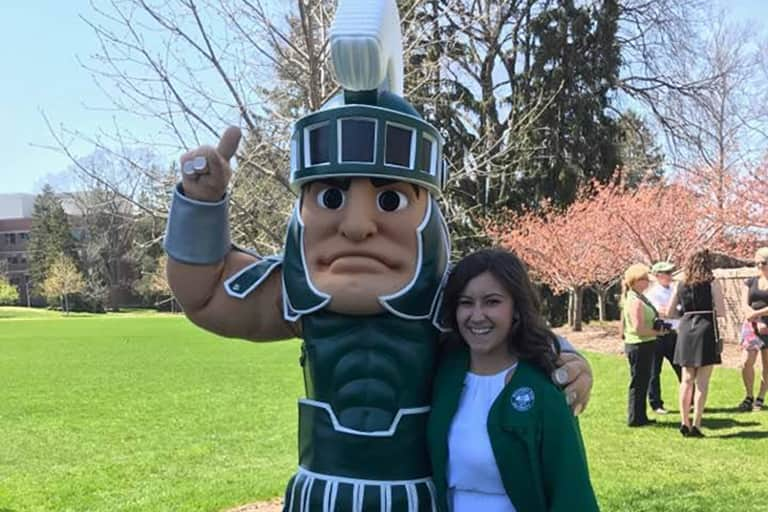 Haley Kluge standing next to Sparty.