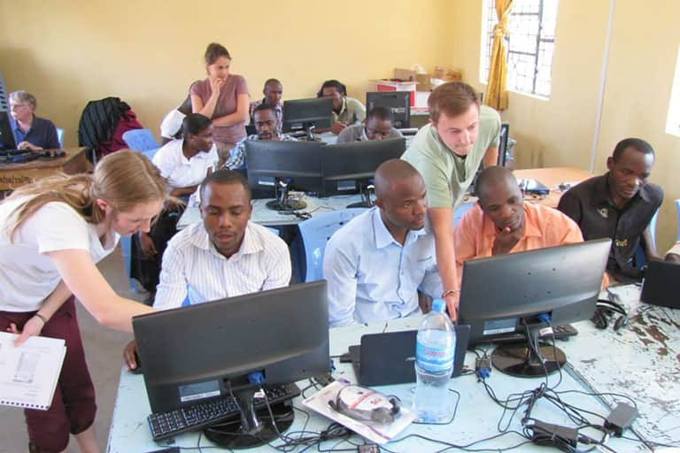 Information and Communication Technologies for Development study abroad students assisting students in the class room on using computer equipment.