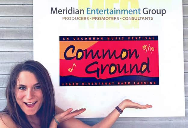 Margaux Koepele smiling and pointing at the Meridian Entertainment Group sign.