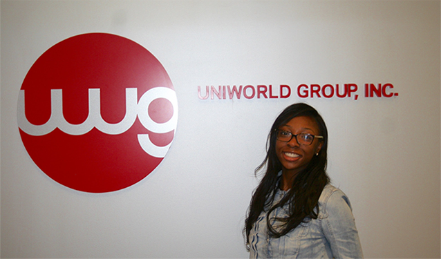 Maya Parnell standing next to Uniworld Group sign.