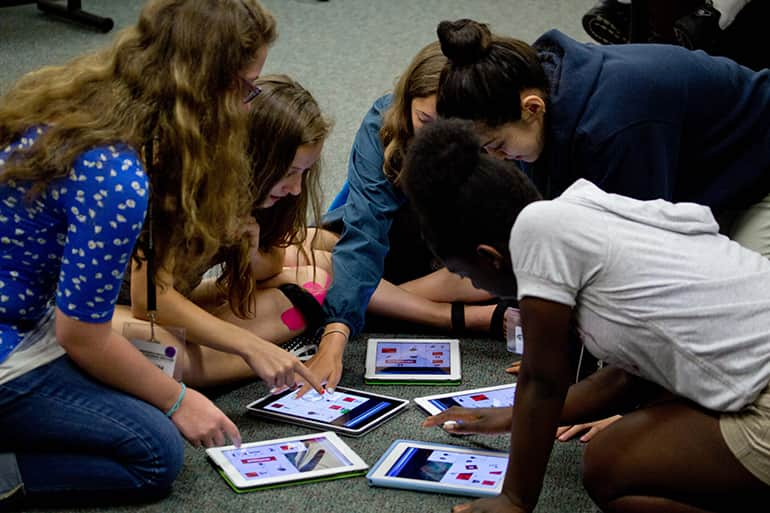 Five girls from the MSU Media Summer Camp are sitting on the floor designing games on iPads.