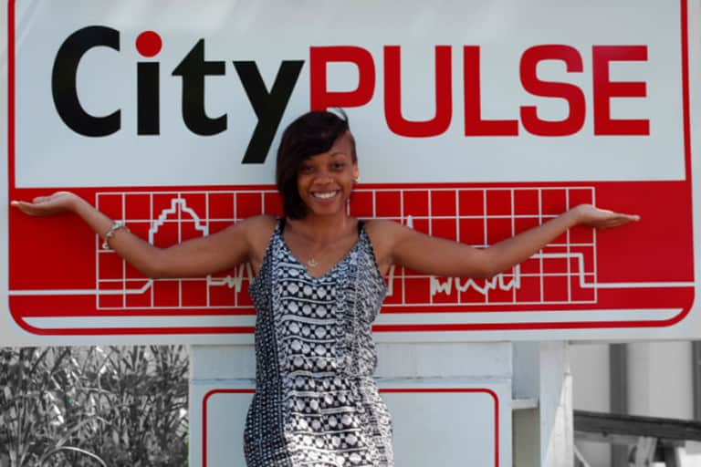 Michelai Graham smiling as she stands outside in front of the City Pulse sign.