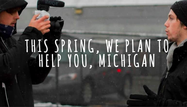 "Photographer taking a photo of a 20 something male. Text on the photo says, ""This spring, we plan to help you, Michigan."""