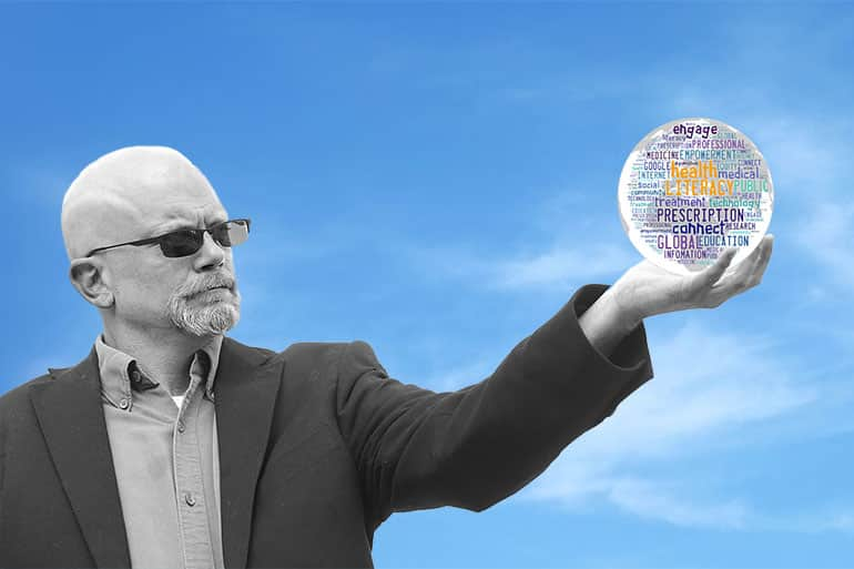 Professor RV Rikard holding a globe in his hand.