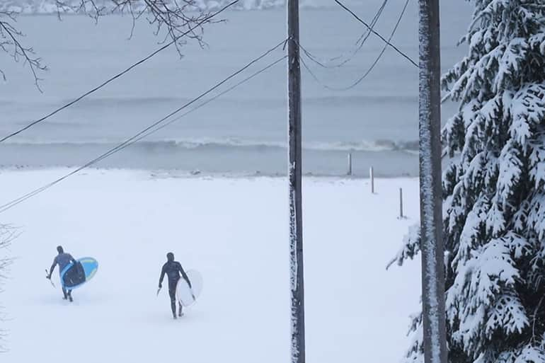 Two athletes walking across the snowy beachs of Michigan's Lake Huron in February preparing to paddle the freezing waves.